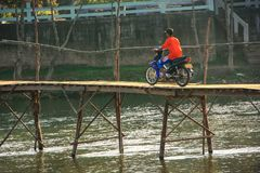 Local man riding motorbike on the bridge in Vang Vieng, Laos Royalty Free Stock Image