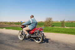 Local man riding a motorcycle on the road Royalty Free Stock Photo