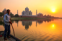 Local man steering boat on Yamuna river at sunset in front of Ta Royalty Free Stock Images