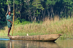 Local man traveling by rowboat at wild river in Chitwan National Park, Nepal Royalty Free Stock Image