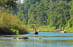 Local man traveling by rowboat at wild river in Chitwan National Park, Nepal. Stock Photo