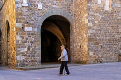 Local man walking in historic center of Montalcino town, Val d`O. Rcia, Tuscany, Italy. The town takes its name from a variety of oak tree that once covered the royalty free stock images