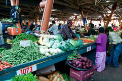 Local market on Mauritius. FLACQ, MAURITIUS-JUNE 23: Indian people and tourists search for a bargains in the market hall on June 23, 2013 in Flacq, Mauritius Royalty Free Stock Image