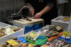Local market, Nipponbashi, Osaka, Japan. Osaka, Japan - November 19, 2016:  Chef is preparing fresh clam at Kuromon Ichiba market, a local market, Nipponbashi Stock Photo