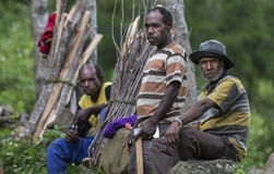 Local men in Baliem Valley. Baliem Valley, West Papua, Indonesia, February 12th, 2016: Locals resting on the side of a road royalty free stock photography