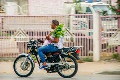Local men riding motorcycle. Punta Cana, Dominican Republic - September 17, 2014: Local men riding motorcycle on street of Punta Cana Stock Photo