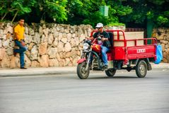 Local men riding motorcycle. Punta Cana, Dominican Republic - September 17, 2014: Local men riding motorcycle on street of Punta Cana Royalty Free Stock Images