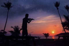 Local musicians, Asian man playing violin on the coconut beach with million stars galaxy. Silhouette artist on purple sky background royalty free stock photos