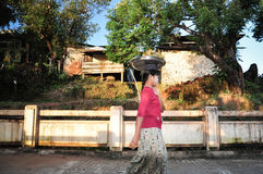 Local Myanmar woman put the stuff on  head while walking Stock Images