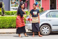 Local native indigenous Polynesian smiling teens, girl and boy, in traditional closing - skirts of taovala and tupenu. Tonga. royalty free stock photo