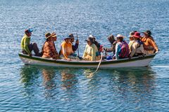 Local native people on a boat. ISLA DEL SOL, BOLIVIA - MAY 12, 2015: Locals native people on a boat at Isla del Sol Island of the Sun in Titicaca lake, Bolivia royalty free stock photo