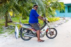 A local native Polynesian man on a motorcycle motorbike with a tuna fish, Tuvalu, Oceania. royalty free stock photography