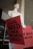Local need over private greed male mannequin  with broadsheet. Public opinion concept social issue local market Royalty Free Stock Photography