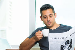 Local news. Copy-spaced image of a young man drinking morning coffee and reading the newspaper at home royalty free stock images