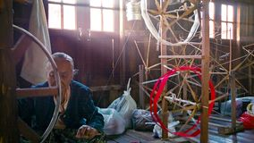 Local old woman working at a textile factory. Production of yarn stock video