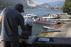 Local painter at work in Stresa, Lake Maggiore. Local artist painting a watercolour paint of Isola dei Pescatori from Isola Bella, Stresa,Lake Maggiore Royalty Free Stock Photo