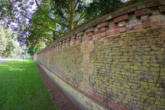 A local park trees with lush foliage along side a brick wall royalty free stock images