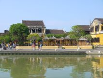 Local people, boats, yellow houses by the river, and tourists in Hoi An ancient town royalty free stock images