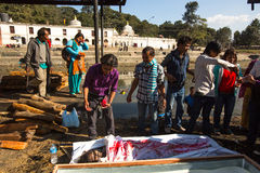 Local people during the cremation ceremony along the holy Bagmati River in Bhasmeshvar Ghat at Pashupatinath temple in Kathmandu. Stock Photos