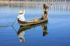 Local people fishing from a boat near U Bein Bridge, Amarapura,. Mandalay region, Myanmar Stock Images