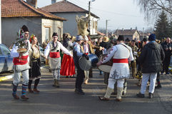 Local people in folk costumes dance on the street. Yardzhilovtsi, BULGARIA – January 14, 2016: Local people gather for Surva celebration with folk and mummers Stock Image