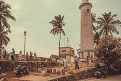 Local people have different business near historical lighthouse. GALLE, SRI LANKA - DEC 23, 2017: Local people have different business near historical lighthouse Stock Photo