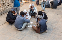 The local people are playing cards in the street. Stock Photo