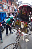 Local people repair tricycle. On the street at Thamel market on October 29, 2013 in Kathmandu, Nepal stock photography