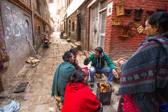 Local people sit in the street. The caste system is still intact today but the rules are not as rigid as they were in the past. BHAKTAPUR, NEPAL - CIRCA DEC Stock Photography