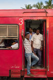 Local people standing in the red train wagon Stock Photos