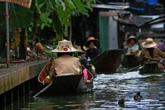 Local people in Thailand living and trading on the river - Damnoen Saduak floating market near Bangkok Stock Photos