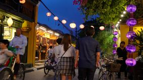 Local people, tourists and bicycle rickshaws at night on the streets of Hoi An, Vietnam stock video footage
