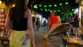 Local people, tourists and bicycle rickshaws at night on the streets of Hoi An, Vietnam. Local people and tourists at night on the streets of Hoi An, Vietnam stock video footage