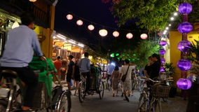 Local people, tourists and bicycle rickshaws at night on the streets of Hoi An, Vietnam stock footage