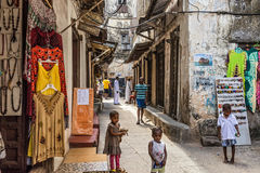 Local people on a typical narrow street in Stone Town, Zanzibar. STONE TOWN, ZANZIBAR - OCTOBER 24, 2014: Local people on a typical narrow street in Stone Town stock images