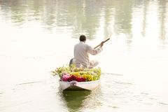 Local people use Shikara, a small boat for transportation in the Dal lake of Srinagar, Jammu and Kashmir state, India. A man carri Royalty Free Stock Images