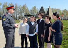 Local police representative tells students about the memorial complex line of Glory. SNEGIRI, RUSSIA - APRIL 29, 2014:Local police representative tells students Stock Photos