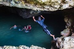 Local Polynesian teens playing and swimming in Veimumuni cave, while a girl jumping to the pool. Motion blur. Vavau, Tonga. royalty free stock photos