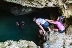Local Polynesian teens swimming in Veimumuni cave, while a small girl shoves a boy to the pool. Motion blur. Vavau, Tonga. royalty free stock photography