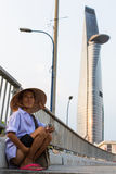 Local poor vietnamese man. HO CHI MINH, VIETNAM - JAN 11, 2016: Local poor vietnamese man, in background Bitexco Financial Tower, 68 floors (and 3 underground) royalty free stock photos