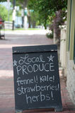 Local Produce: Fennel, Kale, Strawberries & Herbs. A sidewalk chalkboard sign outside a neighborhood grocery store promotes locally grown produce, specifically stock photos