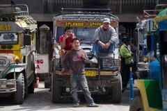 Local public transport jeepney and men. Banaue, Philippines. BANAUE, PHILIPPINES - JAN 24, 2014: Local public transport jeepney and men. Jeepneys passing Royalty Free Stock Photo