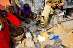 A local repairs a man`s shoe in Jaipur, India. stock photo