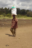 Local resident carries supplies on their head at Nyongara slaughterhouse in Nairobi, Kenya, Africa Stock Photos