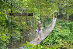 Local Resident Walking on the Suspension Bridge in Tangkahan, In. Donesia. Local resident bought many snacks for tourist to buy. Usually they stand on the side Royalty Free Stock Photography
