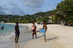 Local residents enjoy sunny day at Grand Anse Beach in Grenada. Royalty Free Stock Images