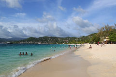 Local residents enjoy sunny day at Grand Anse Beach in Grenada. Royalty Free Stock Photos