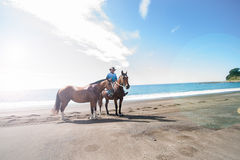 Local riding on beach with two horses Royalty Free Stock Images