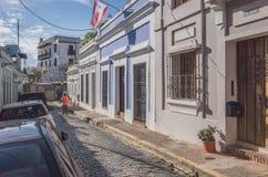 Local riding a bike in old San Juan. San Juan, Puerto Rico, USA - Jan. 2, 2018: A local riding a bike in the street of Old San Juan passing traditional buildings stock photos