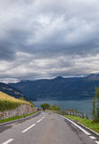 Local road. And view on beautiful lake Thun and Swiss Alps. City of Sigriswil, canton Bern, Switzerland Royalty Free Stock Images